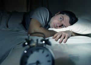 Man having trouble falling asleep